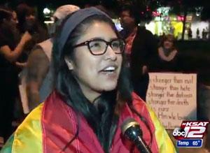A young woman wearing a rainbow flag is among the those at a protest against the Donald Trump presidency at Alamo Plaza on November 11. (Video capture via KSAT-TV)
